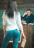 Interested professor looking at his young student. Rear view of girl with long black hair in blue jeans.  Stock Photography