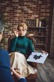 Interested psychologist looking at patient. Serious female advisor is sitting on armchair. She holding tablet with inkblot and showing it to client Stock Image