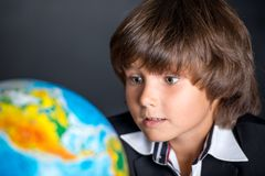 Interested school boy with globe Stock Image