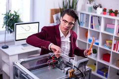 Interested serious scientist touching details of 3d-printer royalty free stock images