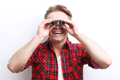 Interested smiling guy looking through binoculars Stock Photo