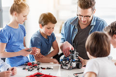 Interested smiling persons creating robot Stock Photography