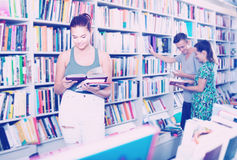 Interested teenager girl reading book in store Stock Photography