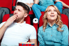 Interested woman and bored man in cinema Stock Photos