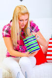 Interested woman looking in shopping bags Royalty Free Stock Photography