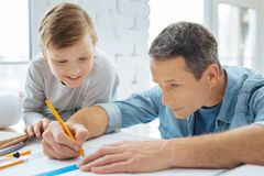 Cheerful boy watching his father sketch blueprint in office Royalty Free Stock Images