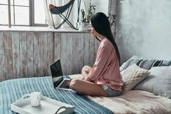 interesting Aantrekkelijke jonge vrouw die computer en het glimlachen gebruiken royalty-vrije stock foto
