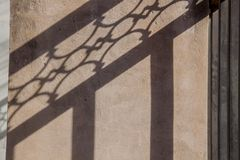 Interesting abstract background with shadow from iron on the wall. royalty free stock images