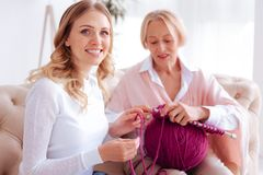 Nice young woman helping her mother to knit. Interesting activity. Nice pleasant young women smiling and helping her mother with knitting while enjoying this Stock Images