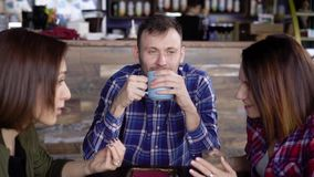 Interesting appearance, an adult man enjoys coffee, which is poured into a blue cup, not paying attention to the two stock footage