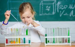Interesting approach to learn. Future scientist. Explore and investigate. School lesson. Girl cute school pupil play. With test tubes and colorful liquids royalty free stock photo