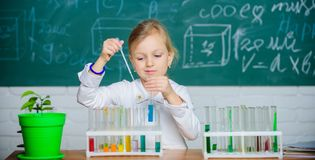Interesting approach to learn. Kid like to experiment. Explore and investigate. School lesson. Girl cute pupil play with. Test tubes and colorful liquids stock photo