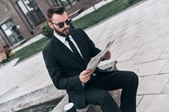 Interesting article. Good looking young man in full suit reading a newspaper while sitting outdoors Stock Photos
