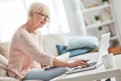 Interesting... Beautiful senior woman writing something down while sitting on the couch at home royalty free stock photography