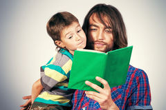 Interesting book. Happy father reading a book to his adorable son royalty free stock photo