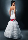 Interesting bride in white dress with red ribbon. Stock Image