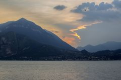 An interesting cloudy sunset - a fairy-beast with an eye-bird and golden contours. Sunset over the majestic Alpine hills, Lake Como region of Lombardy, northern royalty free stock images