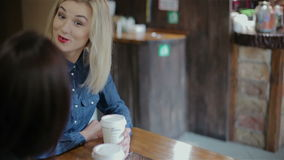 Interesting communicate two girls in coffee shops stock video footage