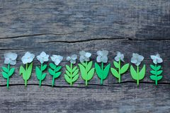 An interesting composition from the plastic stems of flowers and their live inflorescences. Plastic stems of flowers and their live inflorescences, wooden stock image