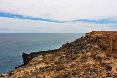 Interesting rock formations by a clear blue sea. Interesting and cool rock formations, part of the petrified forest on the south coast of Australia. Orange and royalty free stock photography