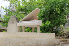 Interesting gravestones along the pathways, this with a piano,Pere LaChaise Cemetery,Paris,France,2016 Royalty Free Stock Photo