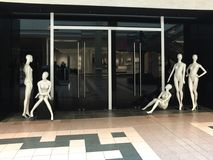 Interesting group of 5 posed mannequins at store closing. In generic shopping mall Royalty Free Stock Photos
