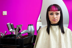 Interesting looking teen girl in hair salon. Interesting looking teen girl with pink hair in sitting in salon chair stock images