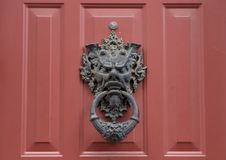 Interesting metal doorknocker, South Philadelphia. Pictured is an old interesting metal doorknocker on a red wooden door in South Philadelphia. It features a stock photography