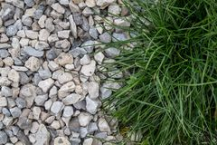 An interesting mix of natural green grass with a solid stone-rubble Stock Photos