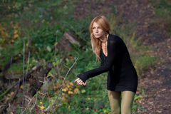 Interesting mysterious blonde walks in autumn forest Royalty Free Stock Photo
