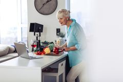 Nice aged woman looking at the laptop screen. So interesting. Nice aged woman looking at the laptop screen while preparing healthy food in the kitchen royalty free stock photography
