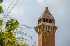 An interesting old stone and brick covered chimney. Covered stone and brick red old chimney, european style, with some green tree branches out of focus Royalty Free Stock Image