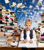 Interesting reading for children. Little boy is reading interesting book. High stacks of books are on the table near him Royalty Free Stock Images