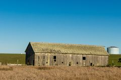 Vintage Barn in Dillon Beach. Blue sky and green fields in background. Brown grass in foreground royalty free stock photos