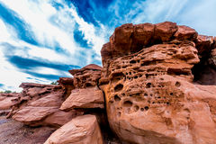Interesting Red Sandstone Rocks in New Mexico. Interesting Red Sandstone Rocks with Holes under Wispy White Clouds and Blue Sky in New Mexico stock image