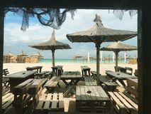 Interesting restaurant near the sea. Tables and chairs put near the sea to be used by tourists when they eat stock image