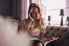 interesting Revista atractiva de la lectura de la mujer joven mientras que siéntese foto de archivo libre de regalías