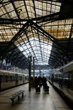 Interesting roof of Waterloo railway station, London, United Kingdom. Silhouettes of the passengers with baggage and trains Royalty Free Stock Photo