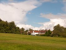 Interesting sloped green lawn with country houses in background. And blue and white cloud sky; England; UK Stock Photography
