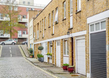 Interesting street partially covered with paving stones, low-ris. E buildings typical of the English quarter, in the distance, tall apartment building, typical Stock Images
