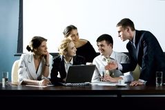 Interesting suggestion. Large group of young businessman gathered together around the laptop discussing interesting question Royalty Free Stock Images