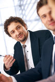 Interesting Talk. Young smiling businessman on the meeting looking and listening to partners Royalty Free Stock Photo