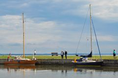 Two big boats moored at the shore, people walking and relaxing stock photography