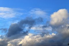 Interesting white and dark mixed cloud formations on a blue sky in spring royalty free stock photography