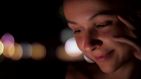 Girl with dark brown hair and eyes sits at night and smiles. Interesting young girl with dark brown hair and large eyes sits at night looks at camera and smiles stock footage