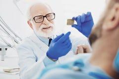 Interesujący męski dentysta daje wyjaśnieniu obraz stock