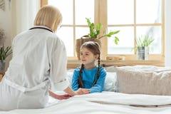 Interesujący pediatra stawia małej ślicznej chorej dziewczyny łóżko fotografia royalty free