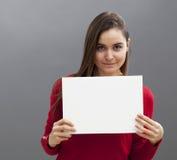 Interesująca uśmiechnięta 20s kobieta robi reklamie w wystawiać pustą wszywkę przed ona Zdjęcia Royalty Free