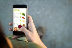 Interfaz en línea del supermercado del smartphone de la mujer que camina imagen de archivo libre de regalías