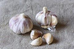 Interi aglio e fette dell'aglio su insaccamento immagine stock